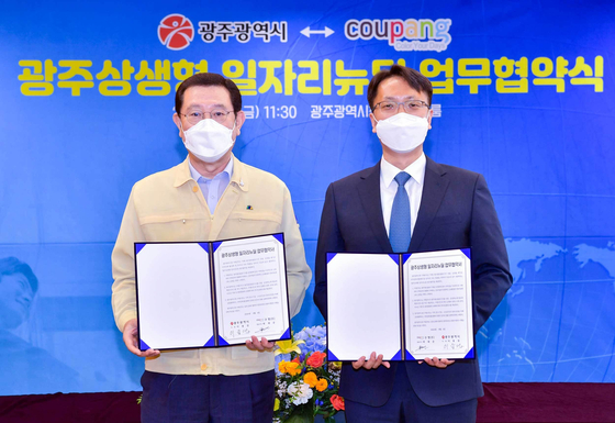 Gwangju Mayor Lee Yong-sup, left, and Park Dae-jun, representative director of the new business division at Coupang, are shown Friday signing an agreement to build a distribution center in Gwangju. [COUPANG]