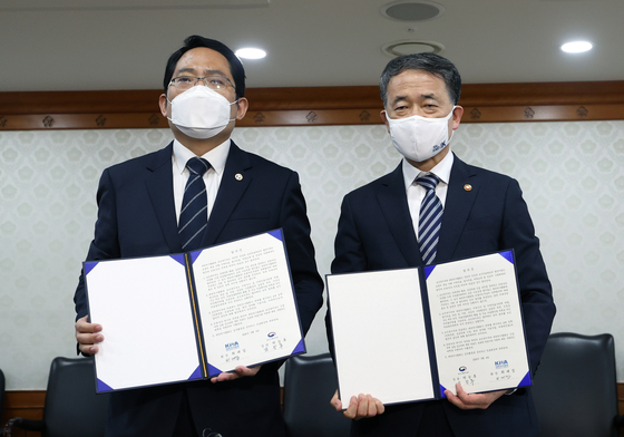 Korean Minister of Health and Welfare Park Neung-hoo, right, and Korean Medical Association President Choi Dae-zip hold up a signed agreement. The two sides agreed to end the strikes in exchange for the government suspending its plans. [YONHAP]