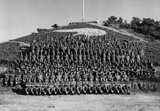 """Gunners from the 16th New Zealand Field Regiment pose for a photograph in front of Kiwi Hill at the regiment's headquarters in Korea in 1953. The photo has been provided by Sue Corkill, author of """"Korea: A Kiwi Gunner's Story,"""" published by Fern Publishing in 2014. [SUE CORKILL]"""