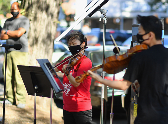"Violinist Quan Ge (left) and violist Cong Wu of the New York Philharmonic play with their ""bandwagon's pop-up concert series"" at Betty Carter Park on Sept. 4 in New York City. [AFP/YONHAP]"