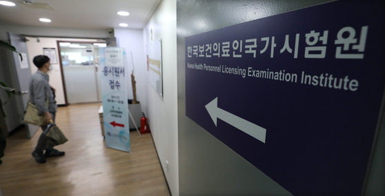A mans stares at the registration sign at the Korea Health Personnel Licensing Examination Institute in Gwangjin District, eastern Seoul, a day before the 85th Korean Medical License Examination kicks off. The Health Ministry said Monday that the medical exam, already postponed once, will be carried out as scheduled despite only 14 percent out of 3,172 medical students having applied for it amid a boycott over increasing medical school admissions. [NEWS1]