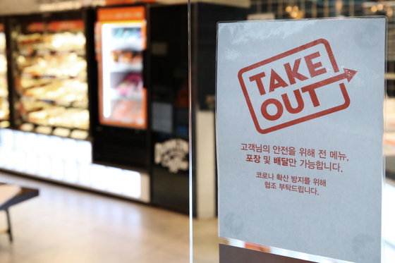 An announcement saying that only deliveries and takeouts are available at a franchise bakery in Seoul on Monday. Along with the government's extended so-called Level 2.5 social distancing measures, bakeries and ice cream chains in the greater Seoul area can't allow their customers to eat or drink inside the store. The restrictions are the same as those already in effect for coffee chains. [YONHAP]