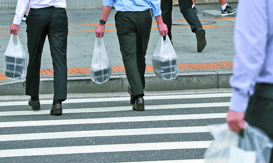 Workers walk to their offices carrying dosirak (packaged meals) in Yeouido, western Seoul, on Sept. 1. [NEWS1]