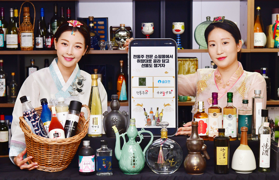 Models promote traditional Korean alcoholic beverages at The Sool Gallery in Gangnam District, southern Seoul, on Monday. Drinks can be ordered online ahead of the Chuseok harvest festival. People who place orders will be given additional gifts such as discount coupons from the Ministry of Agriculture, Food and Rural Affairs and Korea Agro-Fisheries & Food Trade Corporation. [YONHAP]