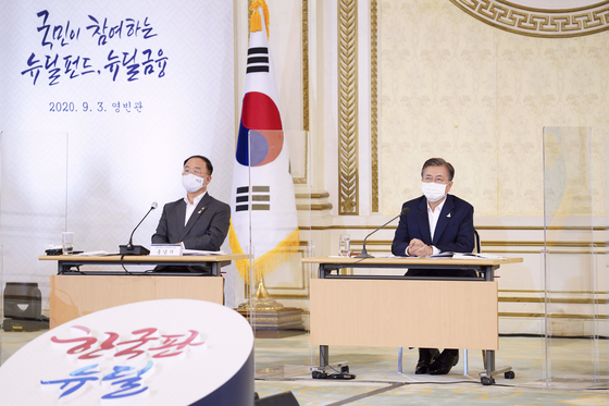 On Sept. 3 at the Blue House, President Moon Jae-in, right, is briefed by Finance Ministry officials on how to create a Korean New Deal fund aimed at drawing investments from ordinary citizens. To his left is Deputy Prime Minister Hong Nam-ki, who also serves as Finance Minister. [JOINT PRESS CORPS]