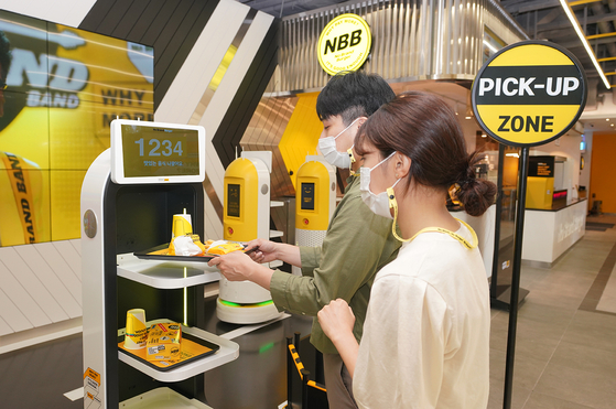 Models pose in front of a robotic waiter at Shinsegae's No Brand Burger branch in Yeoksam-dong, southern Seoul. Shinsegae Food on Tuesday said it has opened a fully automated burger joint where the hamburgers including buns and patties are made on a robotic assembly line. [SHINSEGAE FOOD]