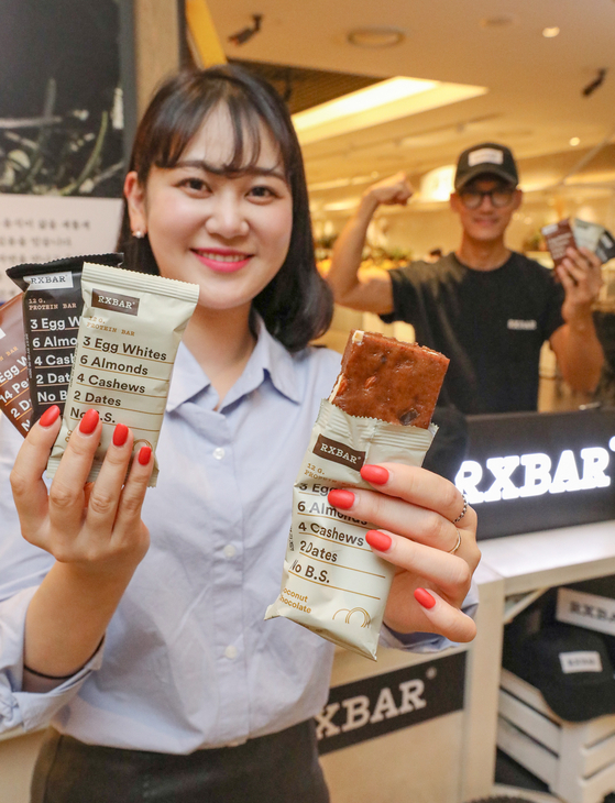 A model holds up RXBAR protein bars at Hyundai Department Store's Coex branch in southern Seoul on Tuesday. Seattle-based RXBAR makes protein bars excluding artificial sweeteners including sugar. [HYUNDAI DEPARTMENT STORE]