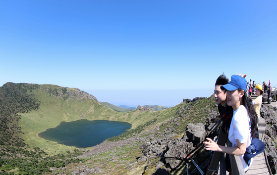 Hikers on Tuesday take in the splendid landscape of Baekrokdam, a crater lake on top of Mount Halla on Jeju Island. The lake was filled with water after recent back-to-back typhoons brought heavy rains on the southern island. [NEWS1]