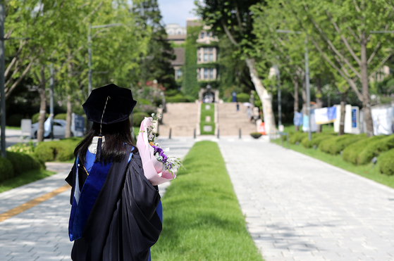A Yonsei University student dressed in gown and graduation cap stands on the campus in Seodaemun District, western Seoul, on Aug. 23. Amid concerns over the spread of the coronavirus, the school canceled its graduation ceremony and only allowed students to take pictures individually with their families. [NEWS1]