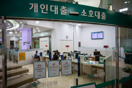 Customers consult with bank clerks on borrowing loans at a Hana Bank in Seoul. [NEWS1]