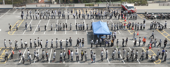 Employees at Hyundai Heavy Industries wait in line at a health center in Ulsan to get tested for Covid-19 on Wednesday after a number of confirmed cases broke out among employees and family members.