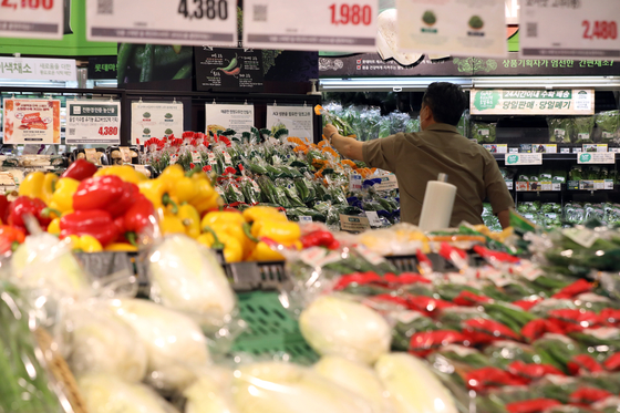 A visitor to a supermarket in downtown Seoul looks at the options in the vegetable section on Sept. 7. [NEWS1]