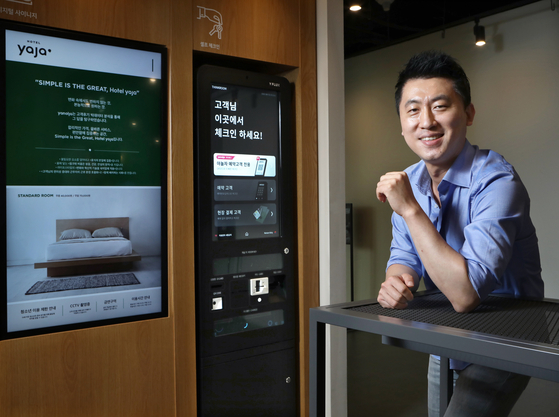 Kim Jong-yoon, Yanolja CEO and head of online business and corporate strategy, poses beside a self-check-in kiosk that allows app users to check in using the Yanolja app, showcased at the company's headquarters in Gangnam District, southern Seoul. [PARK SANG-MOON]