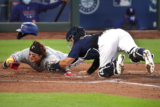 Choo Shin-soo of the Texas Rangers, left, slides to home plate during a game against the Seattle Mariners at T-Mobile Park on Sept. 7. [GETTY IMAGES/YONHAP]