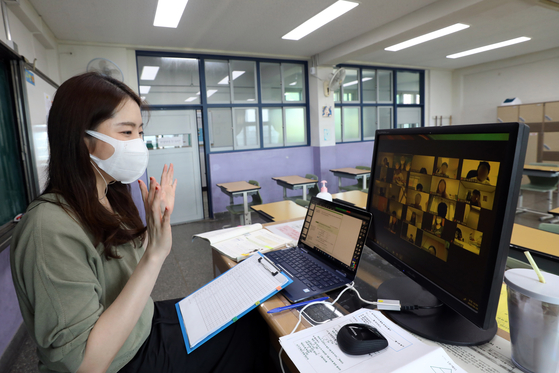 A teacher at Bongeun Middle School in Gangnam District, southern Seoul, conducts an interactive online class with her students on Aug. 26 after schools in the capital area reverted to remote learning because of a spike in coronavirus cases. However, parents are complaining that their children spend most of their time watching prerecorded lessons instead, while some students have yet to have face time with their teachers in the new fall semester. [NEWS1]
