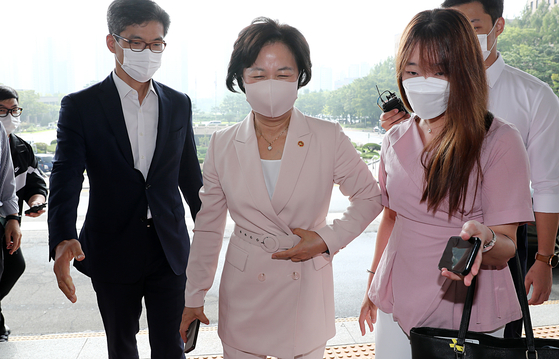 Justice Minister Choo Mi-ae, center, is hounded by reporters as she goes to work at the ministry on Thursday. [YONHAP]