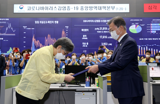 President Moon Jae-in, right, presents Jung Eun-kyeong with a certificate of appointment as the first head of the Korea Disease Control and Prevention Agency during a ceremony held at the emergency situation center of the Korea Centers for Disease Control and Prevention in Cheongju, North Chungcheong, on Friday. Instead of following the tradition of inviting Chung to the Blue House for the appointment ceremony, Moon made a rare visit to her office to present the certificate in an apparent expression of appreciation for her dedicated service during the country's battle against Covid-19. [YONHAP]