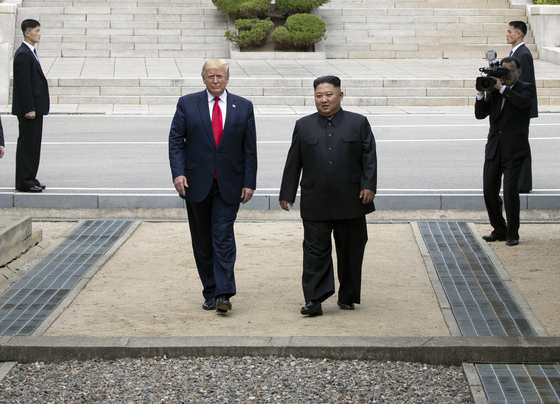 U.S. President Donald Trump, left in center, and North Korean leader Kim Jong-un walk on the North Korean side of the demilitarized zone in their third ― and impromptu ― meeting at the truce village of Panmunjom in June last year. [YONHAP]