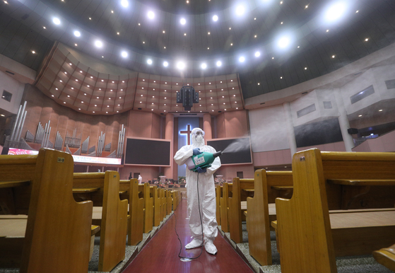 Workers disinfect the Yoido Full Gospel Church in Yeouido, western Seoul, Tuesday, after three adherents tested positive for the coronavirus. All churches in Seoul, Incheon and Gyeonggi have been banned from holding activities, including services and prayer groups, until Aug. 30. [NEWS1]