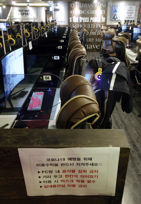 Visitors play online games at an internet cafe in Seongdong District, eastern Seoul, on Monday afternoon. Starting Monday, internet cafes were allowed to reopen nationwide, but with some new restrictions: Minors are not allowed, eating is prohibited and customers must spread out. [YONHAP]