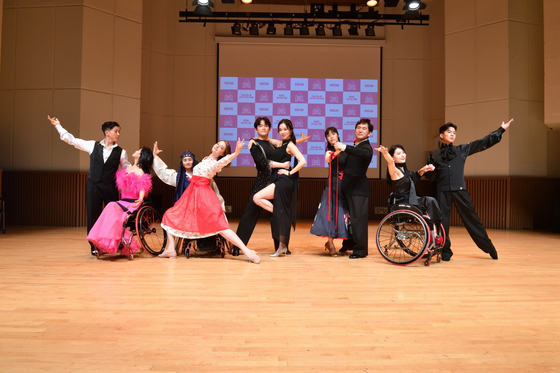 "From left, singer Brian, Russian model Angelina Danilova, singer Kim Na-hee, actor Son Byeong-ho, and singer Na Tae-joo, pose for the camera with their wheelchair dance sport partners at an online press event for the upcoming KBS dance battle show 'Dancing Together"" held Monday."