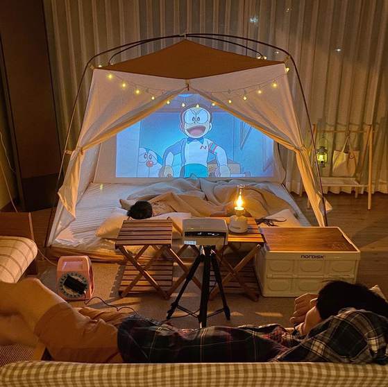 A growing number of people, especially families with children, enjoy camping at home by setting up a tent in the middle of the living room. [NAM JEONG-MIN]