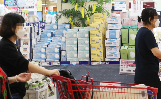 Protective masks stacked up at a retail store in Seoul on Tuesday. The Ministry of Food and Drug Safety said the government will be partially lifting the ban on the exporting of surgical and the lightweight anti-droplet masks due to the steady supply. [YONHAP]