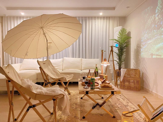 With a few foldable chairs, a table and beam projector, the camping atmosphere is complete. [CHO SU-JEONG]