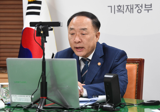 Finance Minister Hong Nam-ki holding a video conference with Asian Development Bank President Masatsugu Asakawa on Monday in Seoul. [YONHAP]
