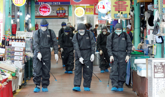 Health care workers spray disinfectant Tuesday at a traditional market in Incheon. [YONHAP]