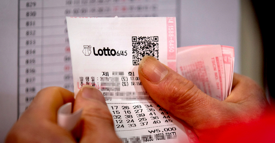 A person is checking their Lotto lottery ticket with the winning numbers. [YONHAP]