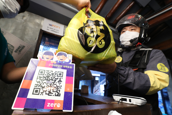 A deliveryman from Ddingdong, a delivery app participating in the Zero Delivery Union initiative, picks up an order from a restaurant in Jongno District, central Seoul. Seoul city launched the Zero Delivery Union service, which charges a 2 percent commission fee, in order to lessen the burden on the self-employed population. The service is initially available with seven small- and medium-sized delivery app companies. [YONHAP]