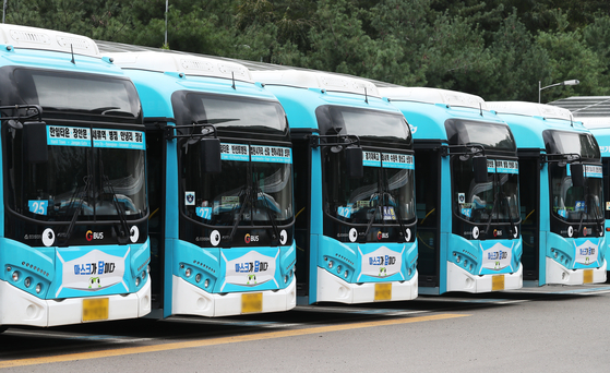 """City buses with mask decals are parked in a public lot in Suwon, Gyeonggi on Wednesday. Suwon recently rolled out its 'Mask is the answer"""" campaign to prevent the spread of Covid-19. [YONHAP]"""