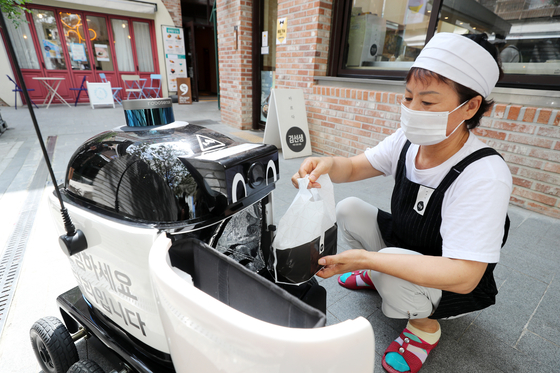 A restaurant employee in Suwon, Gyeonggi, puts food into a delivery robot in August. [NEWS1]