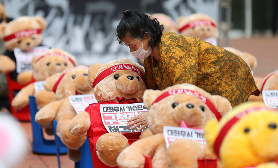 A woman from a union representing street vendors organizes teddy bears in front of Mapo District Office in western Seoul on Thursday in a protest against social distancing measures banning groups of more than 10 people. [YONHAP]