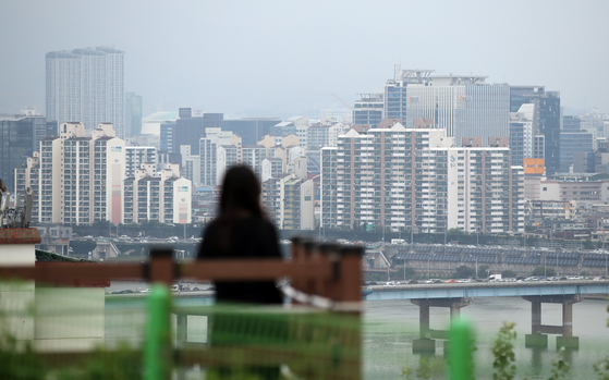A woman looks at apartments in an area south of the Han River on Wednesday. [YONHAP]