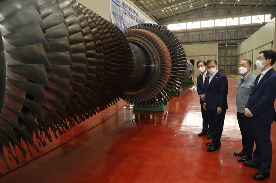 President Moon Jae-in, second from left, views a gas turbine during a tour of Doosan Heavy Industries & Construction at the National Industrial Complex in Changwon, South Gyeongsang, Thursday, as he pushes for his New Deal initiative. [YONHAP]