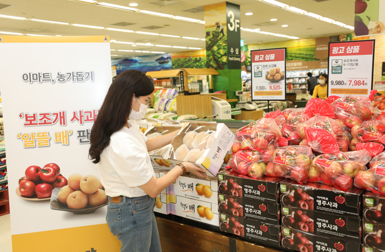 A consumer at Emart's Seongsu branch in eastern Seoul looks at a promotional line of apples and pears, which are cheaper due to their less appealing shapes. [YONHAP]