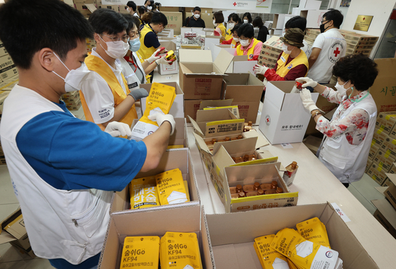 Volunteers organize relief packages that will be given to victims of this summer's heavy rains at Korea Red Cross's Seoul branch at Seongdong District, eastern Seoul, on Thursday. The packages include masks,hand sanitizer, and food products. [YONHAP]