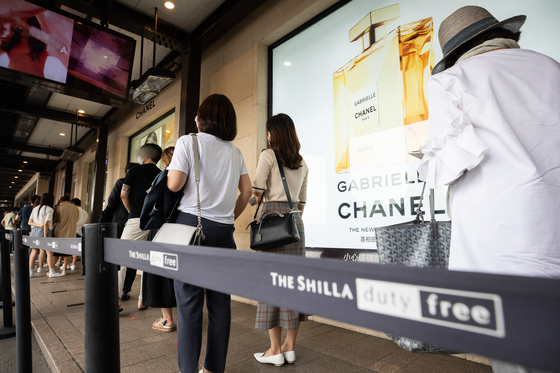 Visitors at Shilla Duty Free in Jangchung-dong in Jung District of central Seoul wait in line on July 21 to shop luxury items that were made available for the public for a limited time in July. [NEWS 1]