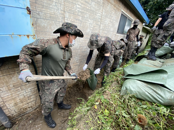 Soldiers from the Korean Army's 22nd Infantry Division take part in typhoon recovery efforts around the house of an elderly veteran in Goseong County, Gangwon, Thursday. [YONHAP]