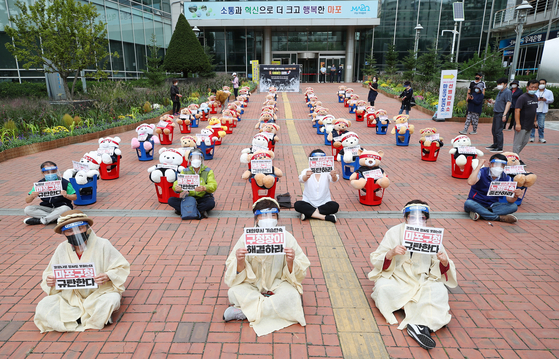 In compliance with social distancing measures banning demonstrations involving 10 people or more in the capital, members of a union representing street vendors in western Seoul protest outside the Mapo District Office on Thursday with dolls. [YONHAP]