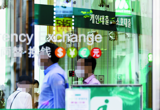People pass by the window of a bank's physical branch in Seoul. [YONHAP]