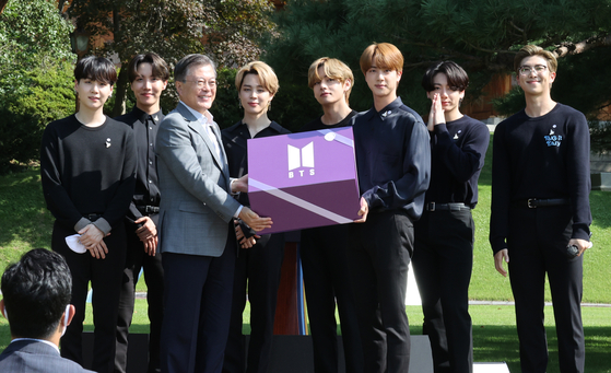 President Moon Jae-in, third from left, poses holding the 'Year 2039 Gift' box with K-pop group BTS at the inaugural Youth Day ceremony at Nokjiwon, a verdant garden inside the presidential compound Blue House, in central Seoul on Saturday. The purple-colored box, which contains musical achievements and messages from BTS members, will be stored at the National Museum of Korean Contemporary History in Seoul, like a time capsule. The box will be opened at the 20th Youth Day event in 2039. At the ceremony, the members of global K-pop superstar BTS delivered a powerful motivational speech for Korean youth, sharing candid tales of their inner struggles on the path to becoming one of the world's most popular music acts in history. [YONHAP]