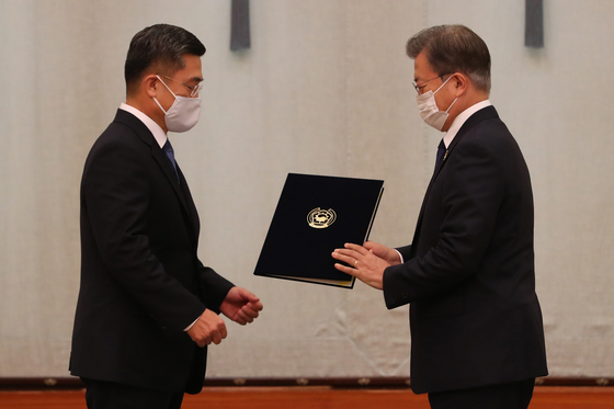 President Moon Jae-in, right, hands an appointment letter to Defense Minister Suh Wook on Friday. [BLUE HOUSE]