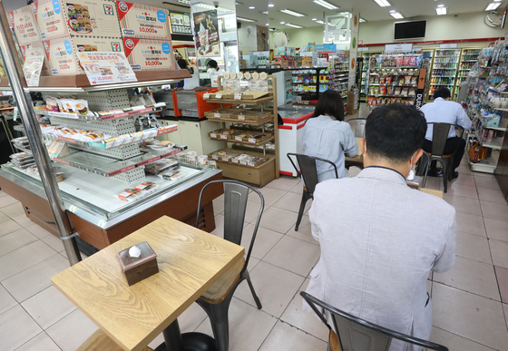 Three office workers are eating doshirak lunch boxes at a convenience store in Jung District, central Seoul, on Sept. 17. [NEWS1]