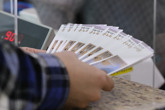 A customer buys Onnuri gift coupons, which can be used to buy products at traditional markets, from a post office in central Seoul on Monday. During Chuseok, the gift coupons are given as gifts. [YONHAP]