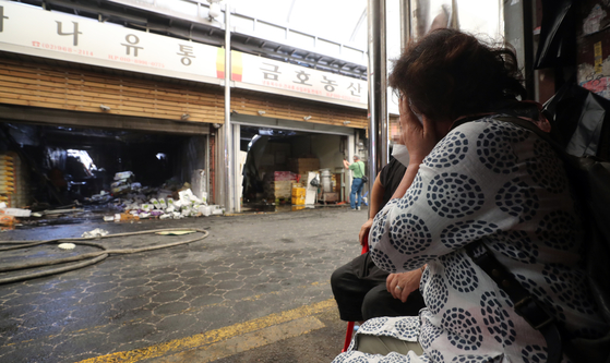 A merchant at the Cheongnyangni grocery market sheds tears in front of a store after a fire swept through the market on Monday. On early Monday morning, a big fire broke out at the traditional market in Dongdaemun District, eastern Seoul. [YONHAP]