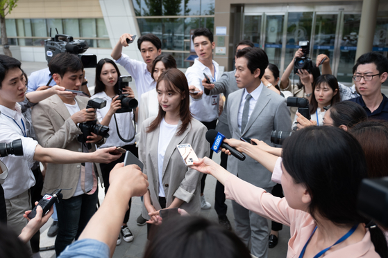 Yi-young surrounded by the press after she leaves the hospital to go back on her training. [MEGABOX PLUS M]