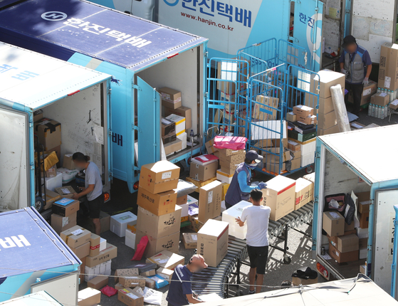 Delivery workers sort packages at a logistic center in Seoul. [NEWS1]